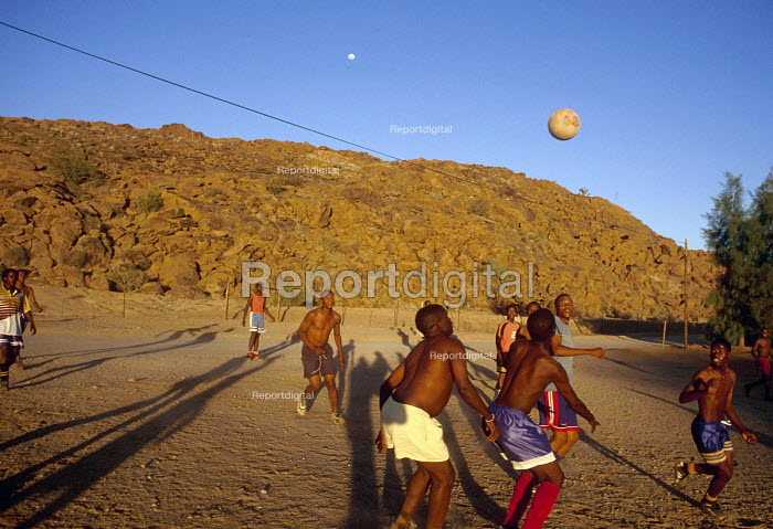 South African farm workers playing football after a days work on a traditionally white owned farm which is entering into a joint ownership partnership with the black workers. South Africa 2003 - Howard Davies - 2003-05-03