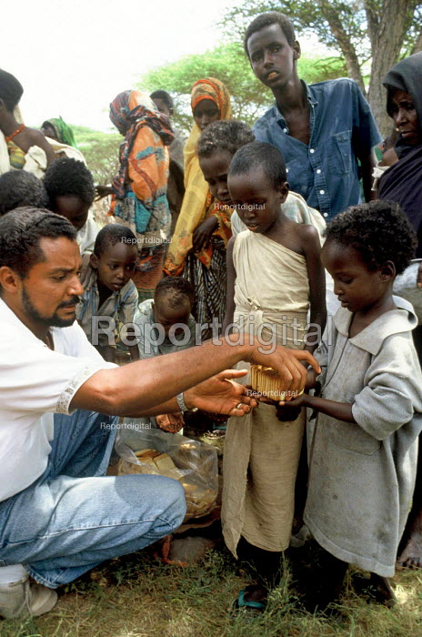 Somali refugee children affected by the famine being assisted by UN aid workers. Somalia - Kenya border. 1993 - Howard Davies - 1993-05-03