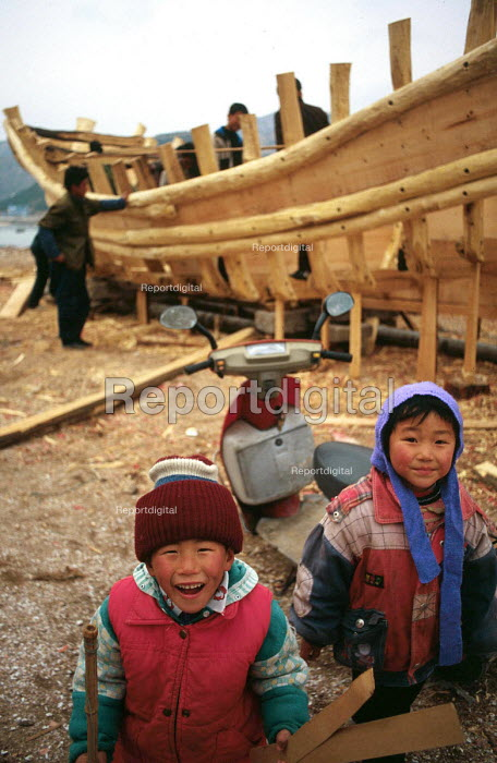 Children with boat building in fishing village in Qingdao District, China. 2001 - Howard Davies - 2001-05-03