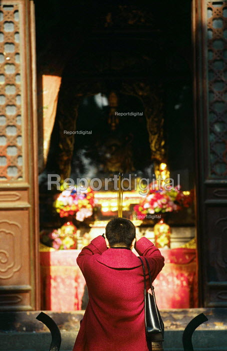 Chinese woman praying at Buddhist temple in Qingdao. China. 2001 - Howard Davies - 2001-05-03