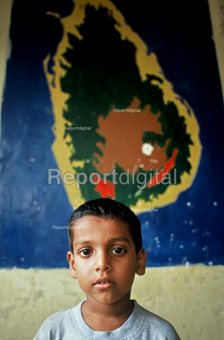 Displaced child survivor of the Tsunami disaster with a map of Sri Lanka at a school converted into an IDP camp in Batticaloa on the east coast of Sri Lanka. Sri Lanka 2005 - Howard Davies - 2005-03-05
