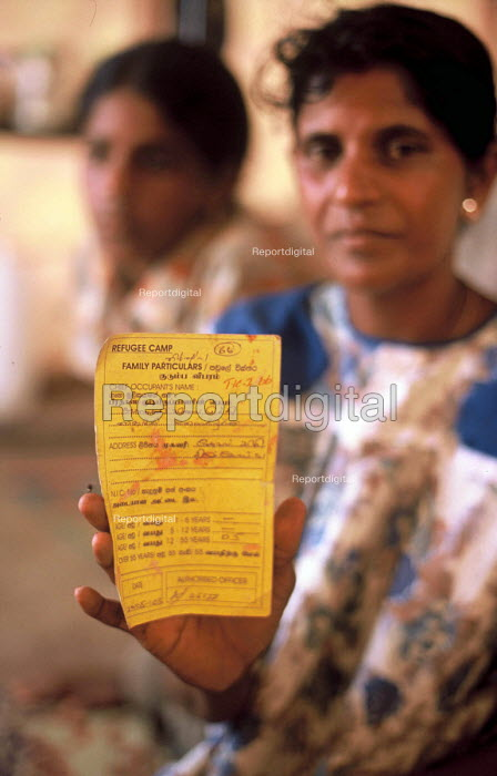 A woman displaced by the Tsunami holds her ID card in the tent her family live in a displaced peoples camp in eastern Sri Lanka. 2005 - Howard Davies - 2005-03-05