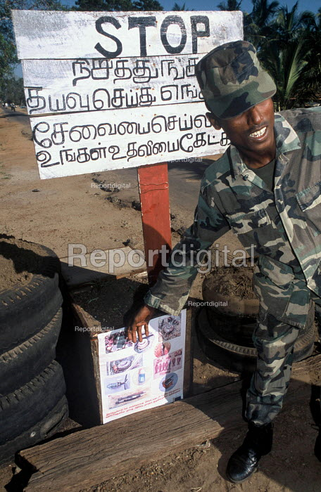 A governemnt soldier shows a poster warning about landmines, many of which were distributed when the nearby army camp to the north of Batticaloa was struck by the Tsunami. Sri Lanka 2005 - Howard Davies - 2005-03-05