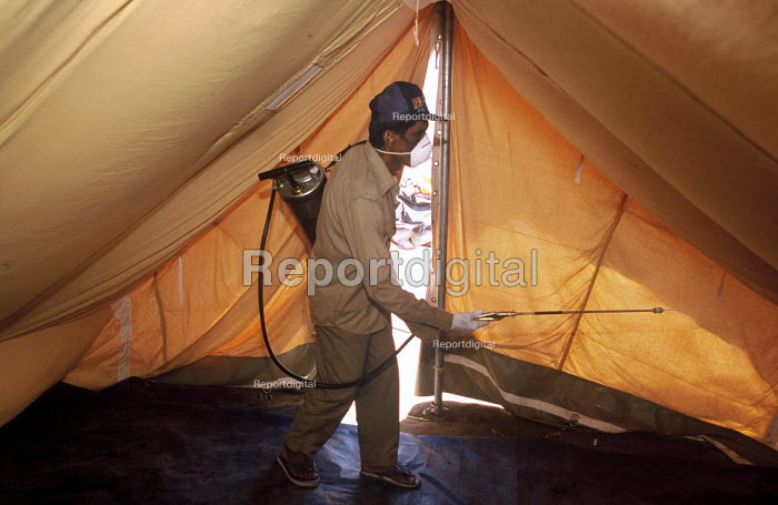 Spraying against mosquitoes to stop spread of malaria and dengue fever in camps for families displaced by the Tsunami, a programme implemented by the local health office but financed by Oxfam. Vattavan camp, north of Batticaloa, Sri Lanka. 2005 - Howard Davies - 2005-03-05