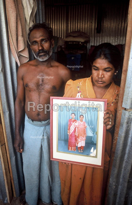 A Tamil couple in a displaced peoples camp hold a photograph of the two children she lost in the Tsunami. Batticaloa district, Sri Lanka. 2005 - Howard Davies - 2005-03-05