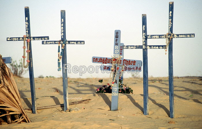 The graves of more than seventy villagers lost in the Tsunami, on a sand dune high above the village, Jaffna district, Sri Lanka 2005 - Howard Davies - 2005-03-05