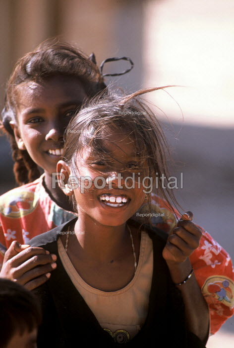 Tamil children, whose families were displaced by the Tsunami, playing outside temporary shelters, Batticaloa district, Sri Lanka 2005 - Howard Davies - 2005-03-05