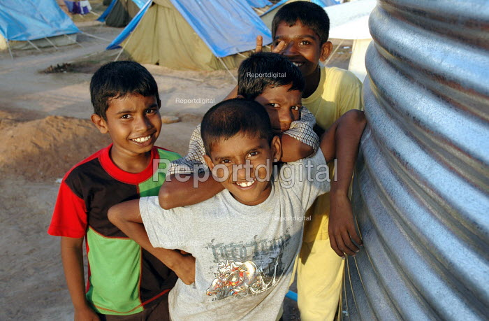 Children displaced by the Tsunami stand by an Oxfam water tank providing clean drinking water for families living in an IDP in Tirukkovil District, Sri Lanka. 2005 The provision of clean drinking water prevents water borne disease. - Howard Davies - 2005-03-05
