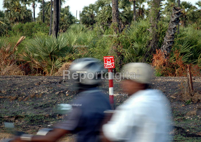 A motorbike passes a sign for a landmine field in northern Sri Lanka where hundreds of thousands of landmines and ordnance litter the countryside. Jaffna district, Sri Lanka 2005 - Howard Davies - 2005-03-05