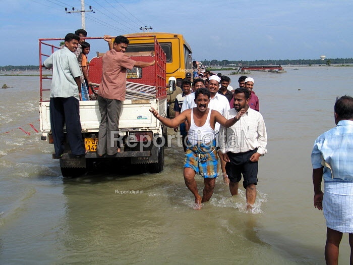 Survivors of the Tsunami negotiate flooded roads to the south of Batticaloa. The severe and early monsoon compounded the devastating effects of the Tsunami leaving many areas of the east coast flooded and hindering the aid effort. Sri Lanka 2005 - Howard Davies - 2005-03-05