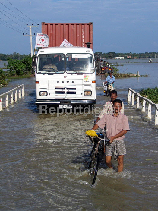 A Red Cross truck delivering aid supplies negotiates flooded roads to the south of Batticaloa. The severe and early monsoon compounded the devastating effects of the Tsunami leaving many areas of the east coast flooded and hindering the aid effort. Sri Lanka 2005 - Howard Davies - 2005-03-05
