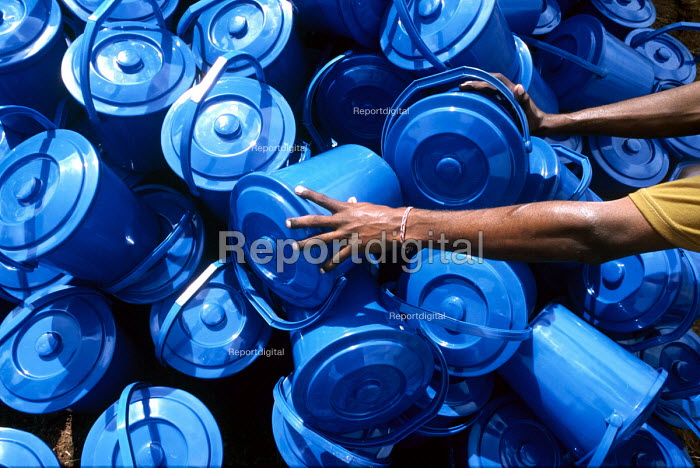 Blue buckets part of an Oxfam hygiene kit being prepared for distribution to displaced people survivors of the Tsunami disaster who receive non food essentials in IDP camps to the north of Batticaloa on the east coast of Sri Lanka. The provision of hygiene kits and clean drinking water is intended to avert disease spreading through the camps. Sri Lanka 2005 - Howard Davies - 2005-03-05