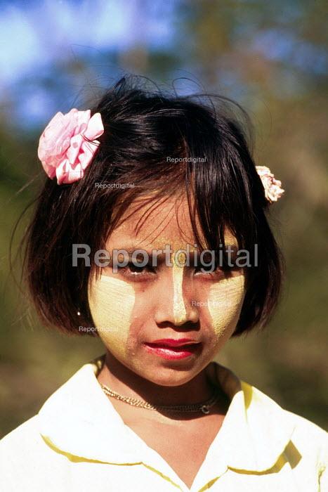 Burmese girl using traditional wood paste, Thanaka cream, on her face. Mingun Pagoda near Mandalay, Burma. - Howard Davies - 1997-08-03