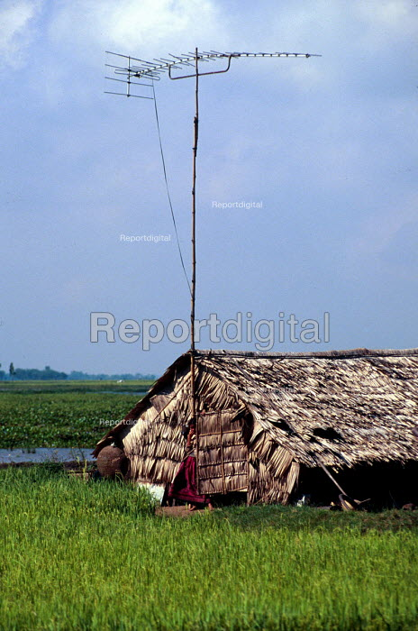 Small rural holding with TV aerial. Takeo district, Cambodia. 2001 - Howard Davies - 2001-08-03