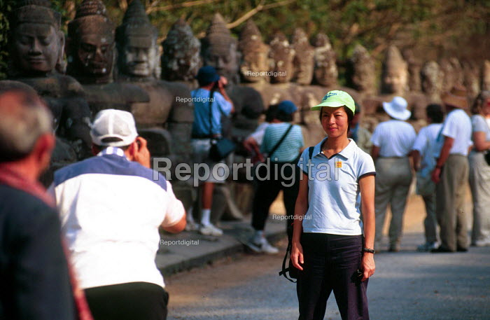 Tourists being photographed in front of the South Gate of Angkor Thorn, at Angkor Wat. - Howard Davies - 2001-05-03