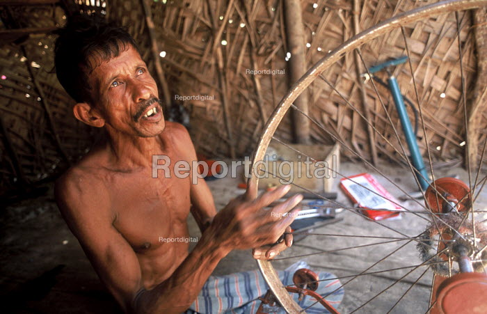A man who has received a cash grant from Oxfam following the tsunami to restart his bicycle repair business. Batticaloa district, Sri Lanka 2005 - Howard Davies - 2005-11-03