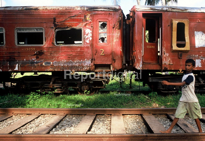 A boy walks along the newly repaired tracks past the damaged Galle - Colombo train which was hit by the Tsunami with the loss of 1500 passengers. Sri Lanka 2005 - Howard Davies - 2005-11-03