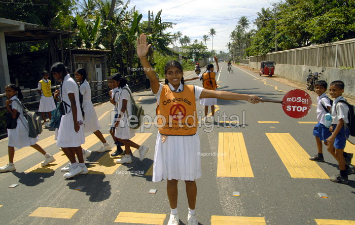 Specially trained pupils acting as crossing wardens to enable other children to cross the road to the school safely. Sri Lanka 2007 - Howard Davies - 2007-10-23