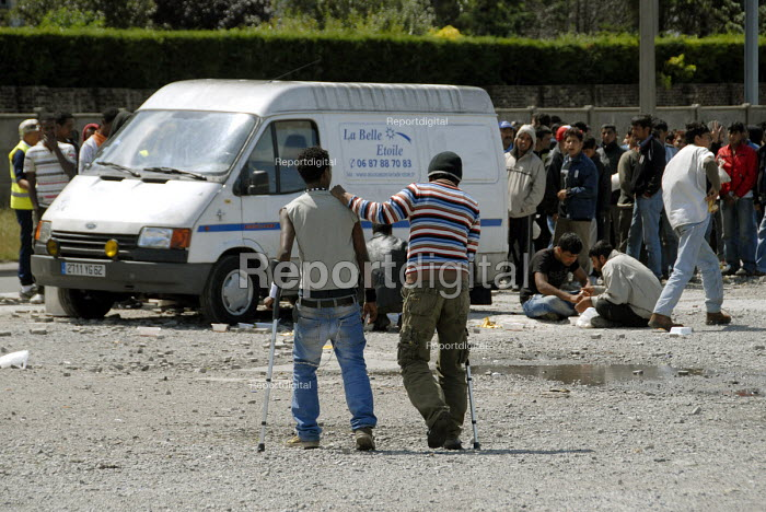 Asylum seekers who are camped near the port of Calais wait for volunteers from local aid agency La Belle Etolie to make a food distribution in a car park in Calais, France 2009 - Howard Davies - 2009-07-17
