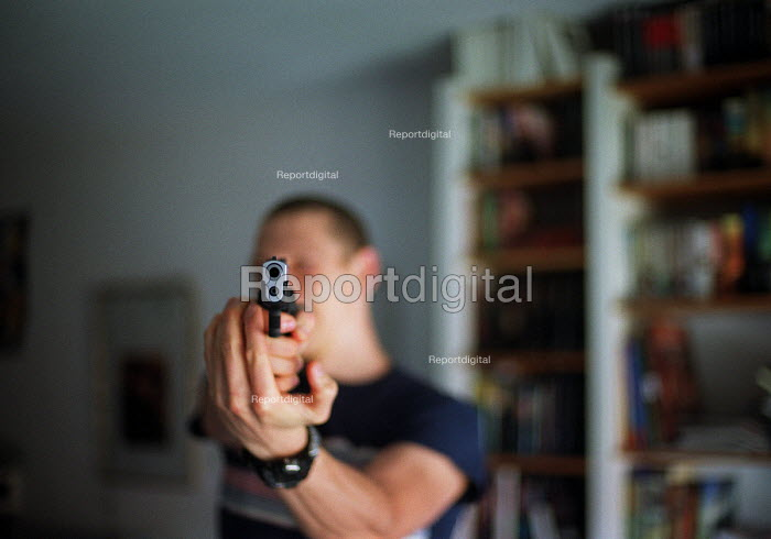 Young man pointing a handgun. - Timm Sonnenschein - 2003-08-20