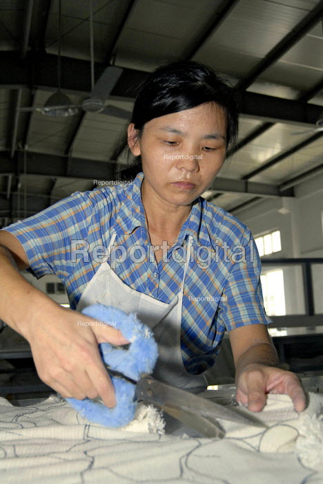 A woman preparing fabric for further production in the 'Toy Home' soft toy factory in Shanghai - Timm Sonnenschein - 2006-09-01