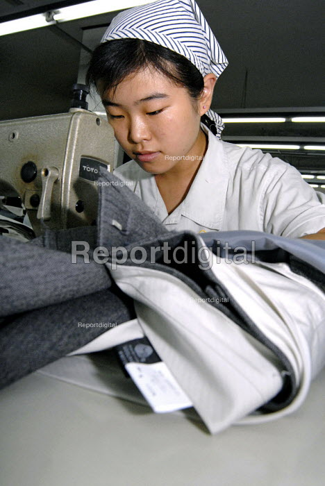 A worker sewing trousers for export in a textile factory in Shanghai - Timm Sonnenschein - 2006-08-25