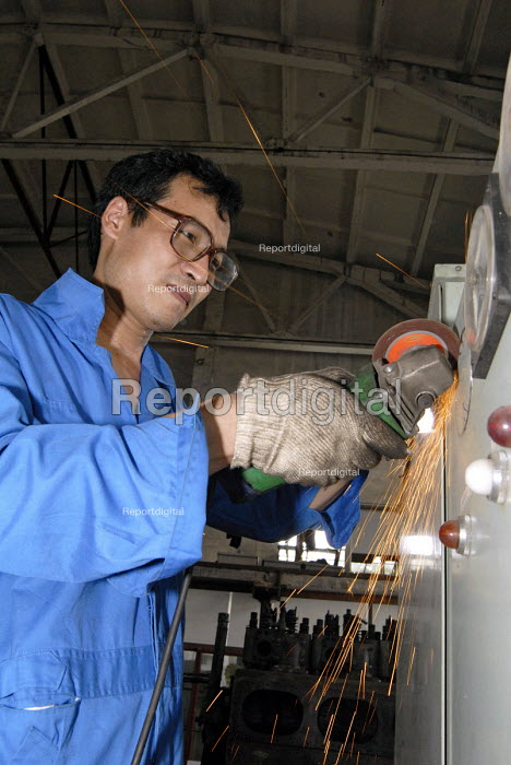 A Chinese man using an angle grinder in a wharf in Pudong, Shanghai - Timm Sonnenschein - 2006-08-17