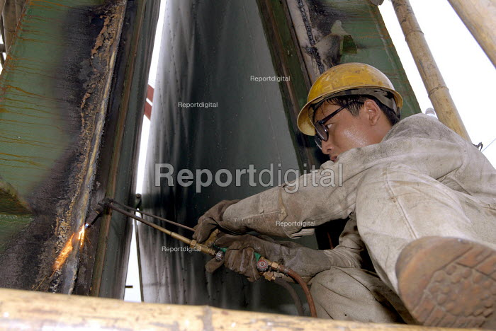 Chinese worker welding on a ship in a wharf in Pudong, Shanghai - Timm Sonnenschein - 2006-08-17