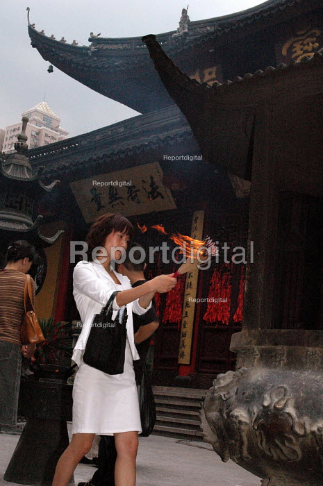 Young woman offering incense at the Jade Buddha Temple, Shanghai, China - Timm Sonnenschein - 2005-09-12