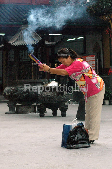 Woman offering incense at the Jade Buddha Temple, Shanghai, China - Timm Sonnenschein - 2005-09-12