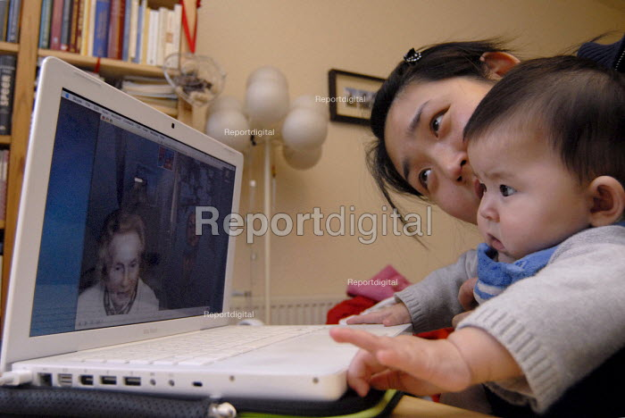 Mother and her mixed race baby are meeting grandmother and great grandmother from Germany on Skype - Timm Sonnenschein - 2007-12-25