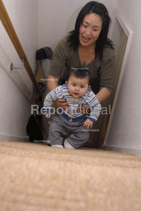 Chinese mother climbing up stairs with her mixed race baby - Timm Sonnenschein - 2008-01-05