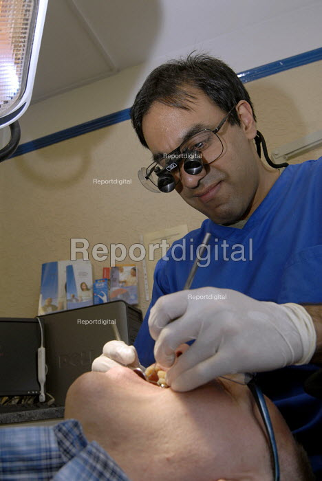 A young dentist treating a patient in his practice in Redditch - Timm Sonnenschein - 2008-07-25