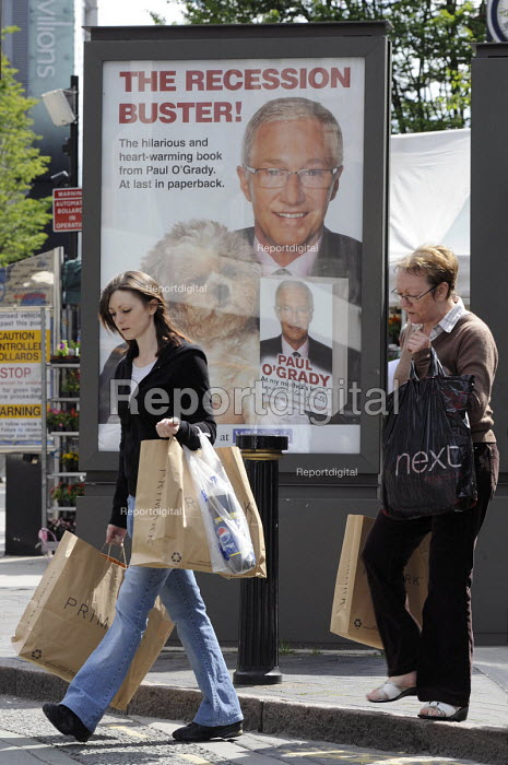 Shoppers walk past The Recession Buster by Paul OGrady, an advertisement by WH Smith for the autobiography of Paul OGrady now in paperback, Birmingham - Timm Sonnenschein - 2009-06-11