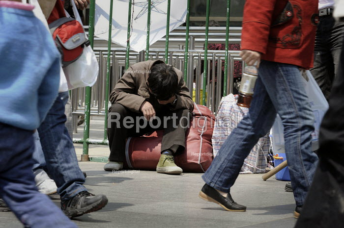 Migrant workers waiting outside the railway station to leave Shanghai, China and return to the countryside as jobs are lost during recession - Timm Sonnenschein - 2009-04-09