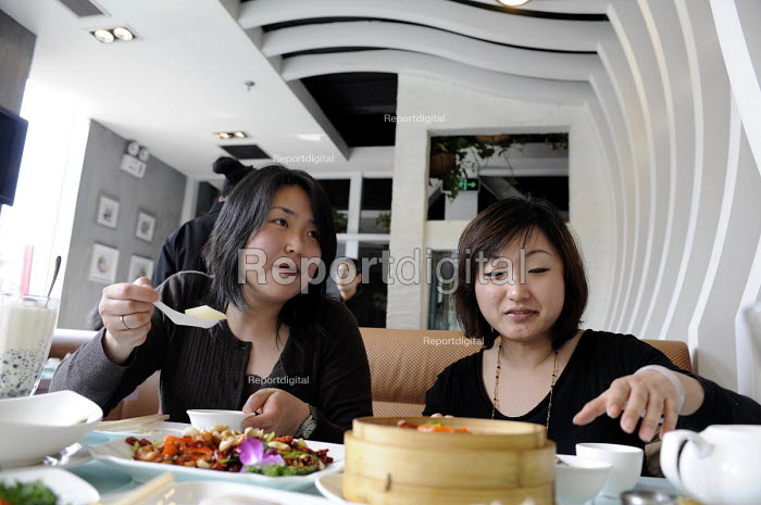 Two young women eating in a modern expensive restaurant in Shanghai, China - Timm Sonnenschein - 2009-04-08