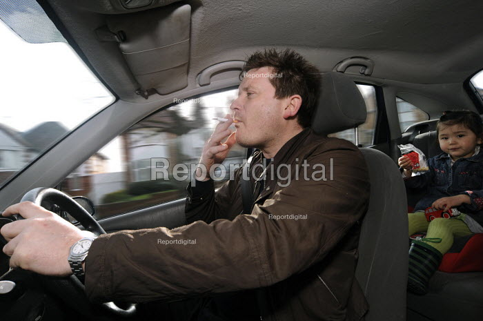 Smoker driving his car with a child on the back seat. Doctors demand a review of anti-smoking laws to consider a ban on smoking in all cars to protect the young from second-hand smoke - Timm Sonnenschein - 2010-03-28