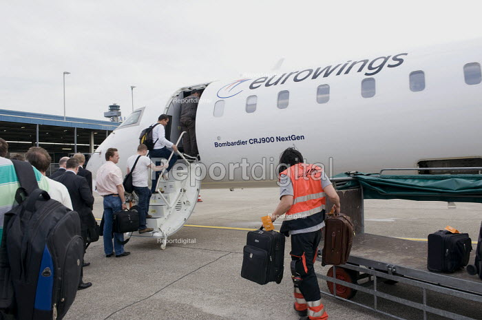 A young Chinese migrant worker is loading bags and suitcases on a Eurowings/Lufthansa plane to Dusseldorf as passengers are boarding, Birmingham International Airport - Timm Sonnenschein - 2010-05-25