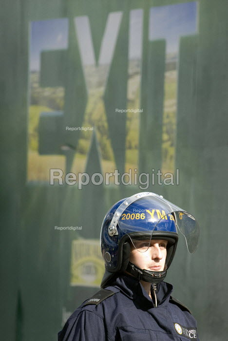 Police officer in riot gear with an advertisement saying Exit, Dudley - Timm Sonnenschein - 2010-07-17