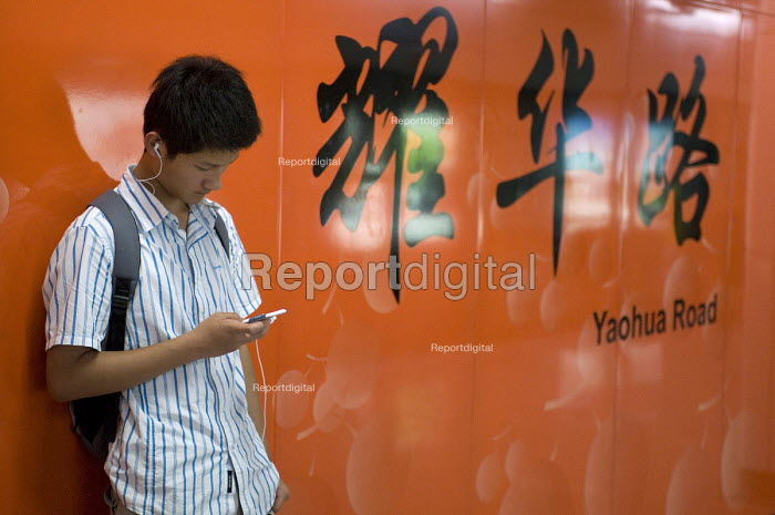 A young man listening to his MP3 player waiting for the Shanghai Metro, Yaohua Road, Shanghai - Timm Sonnenschein - 2010-07-29