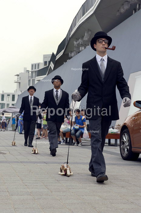 Performers walk outside the English pavilion during the Expo 2010, Shanghai with bowler hats and walking toy dogs. - Timm Sonnenschein - 2010-07-29