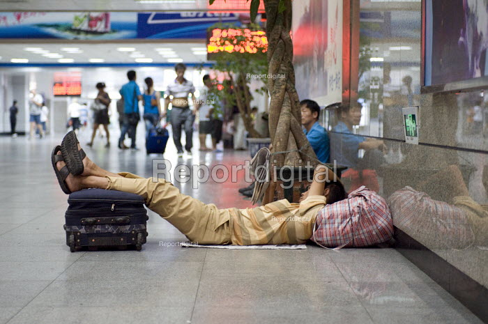 A migrant worker reading whilst waiting for his train home, Wuxi railway station, China - Timm Sonnenschein - 2010-08-17