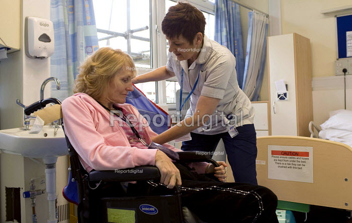An NHS rehab assistant helping a patient into a hoist in order to lift her from her wheelchair, Moseley Hospital, Birmingham - Timm Sonnenschein - 2010-11-18