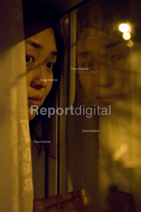 A Chinese woman at the window watching the street at night - Timm Sonnenschein - 2010-12-02