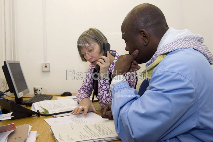 A volunteer worker making a phone call on behalf of a man seeking advise at the Birmingham Citizens Advice Bureau, which is facing closure due the Birmingham City Council withdrawing 600,000 funding for all five walk in advice centres in the city - Timm Sonnenschein - 2011-02-04