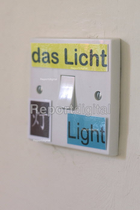 Light switch with labels saying light in English, German and Chinese as a learning tool for a trilingual child growing up with these languages. - Timm Sonnenschein - 2011-03-09