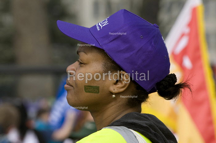 A UNISON member with cap and stenciled face, �during the TUC March For the Alternative, London - Timm Sonnenschein - 2011-03-26