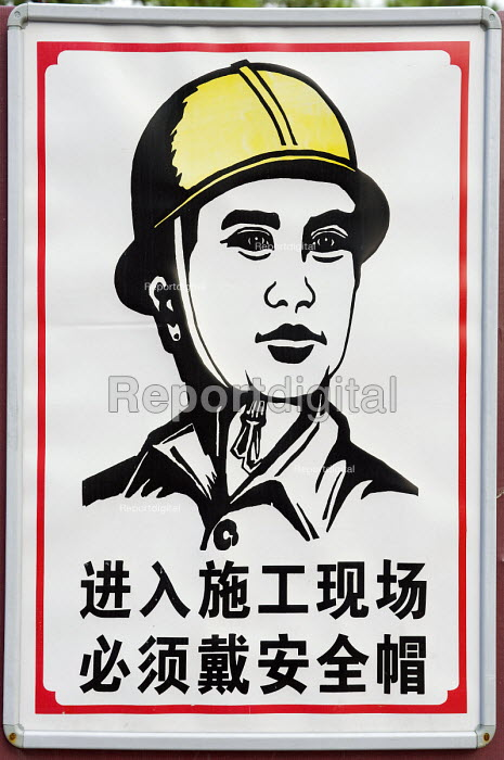 A sign reading You must wear a safety helmet when you enter the construction site. China - Timm Sonnenschein - 2011-08-02
