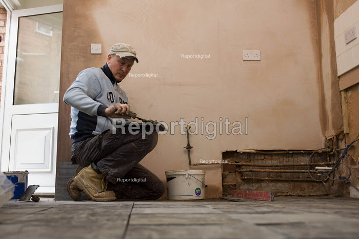 A Polish builder laying slate tiles in a domestic kitchen. - Timm Sonnenschein - 2011-11-14