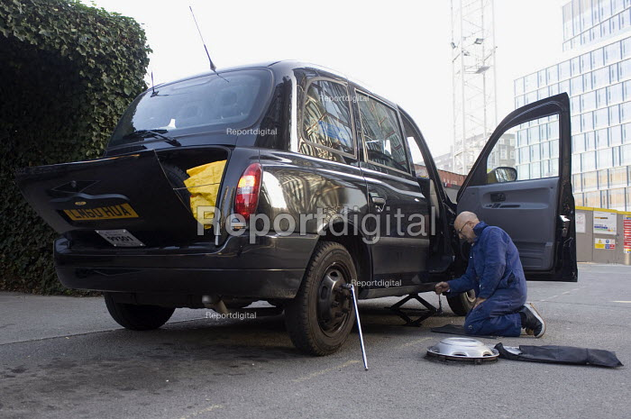 A taxi driver changing a flat tyre, replacing it with a spare. London. - Timm Sonnenschein - 2011-11-20